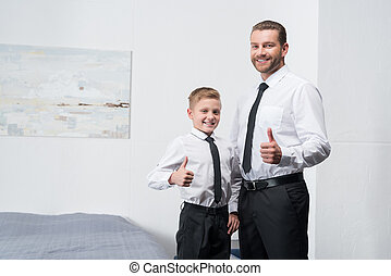 father and son in formal wear - happy father and son in...