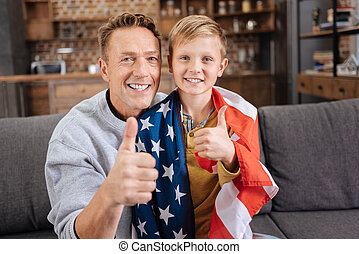 Happy father and son in US flag showing thumbs up