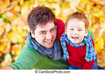 happy father and son making selfie among fallen leaves