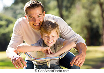 happy father and son on a bike - portrait of happy young...