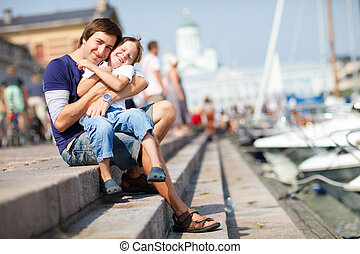 Happy father and son sitting on pier in city center