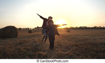 Happy father and son playing airplanes in nature