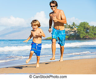 Happy father and son playing and running together at beach