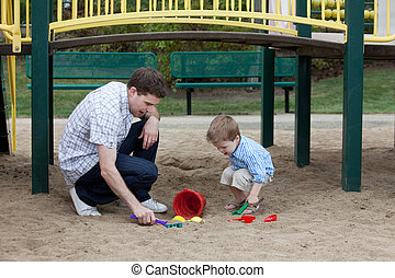 Father And Son Playing At Playground In Sand
