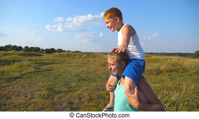 Happy father and son playing on the field at sunny day. Little boy sitting on shoulders of his daddy and playing raised hands as airplane. Dad and child having fun together. Slow motion