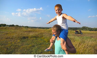 Happy father and son playing on the field at sunny summer...