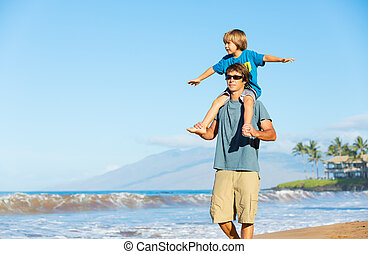 Happy father and son playing on tropical beach, carefree happy fun smiling lifestyle