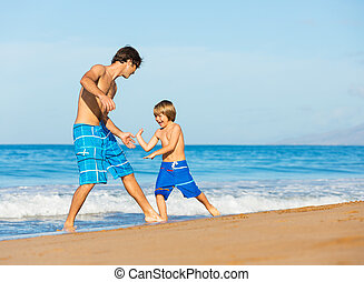Happy father and son playing together at beach