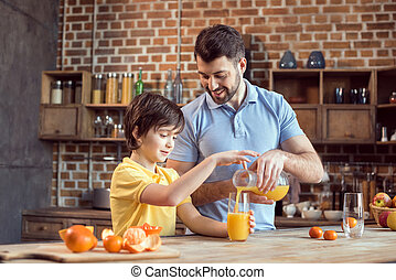 father and son pouring fresh juice in glass