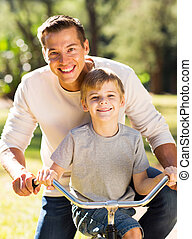 father and son riding a bicycle