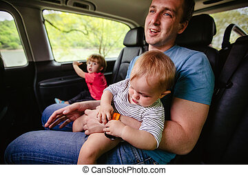 happy father and son sitting together in car
