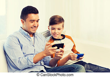 happy father and son with smartphones at home - leisure,...