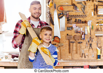 happy father and son with wood plank at workshop - family,...