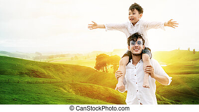 Happy father carry son on shoulders on vacation.
