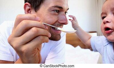 Happy father feeding his baby son