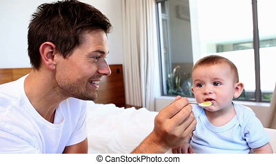 Happy father feeding his baby son
