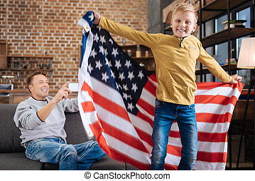 Happy father filming his son jumping with US flag