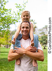 Happy father giving his daughter piggy-back ride in a park