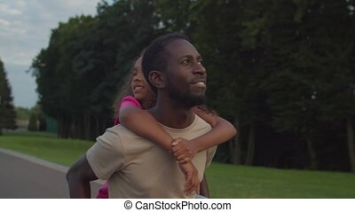 Happy father giving piggyback ride to little girl - Portrait...