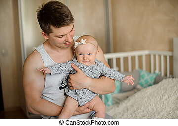 Happy father holding a newborn baby girl in his arms