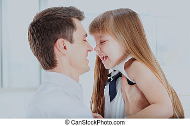 Happy father holding daughter on hands laughing turned to his face.
