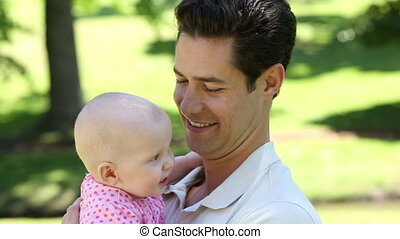 Happy father holding his baby girl in the park on a sunny...