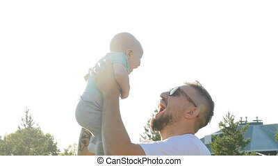 Happy father holding his son at sunset