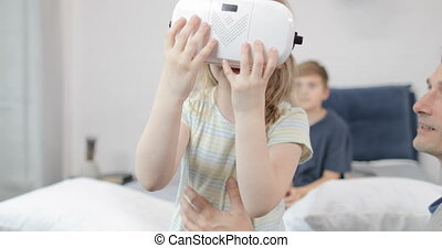 Happy Father Holding Little Girl Wearing Virtual Reality...