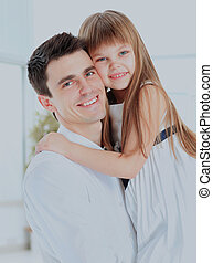 Happy father holding smiling daughter in his arms.