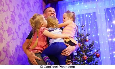 Happy father holds on the hands of children, smiling and laughing in a Christmas evening. In the background, lights and garlands of Christmas fir