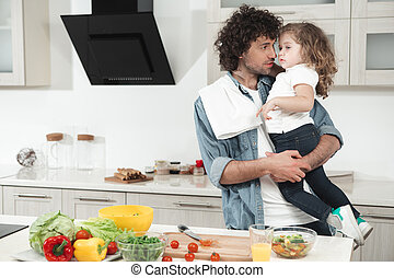 Happy father hugging his daughter in cook room