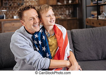 Happy father hugging his son in US flag