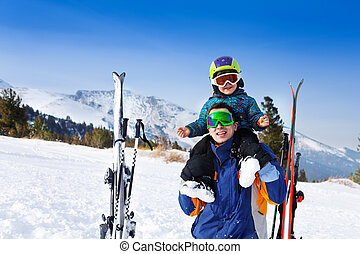 Happy father in ski mask with son on shoulders