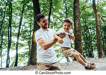 Happy father is circling in the arms of his young son.