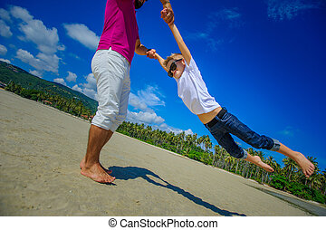 Happy father is spinning in circle his adorable boy. Sunny tropical beach, palm trees behind