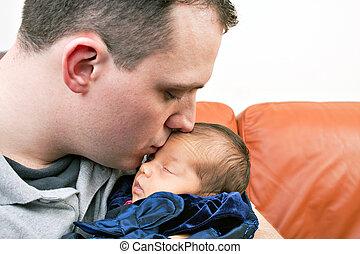 Happy Father Kisses His Newborn Baby