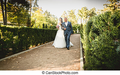 Happy father leads bride to the altar at park - Happy father...