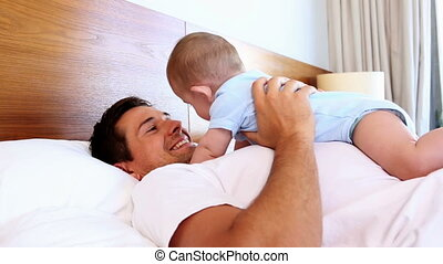 Happy father lying with baby son