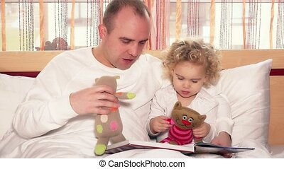 Happy father man playing with lovely daughter girl using toy cats