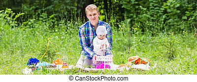 Happy father play with adorable little baby daughter in nature