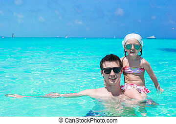 Happy father play with little daughter in perfect sea