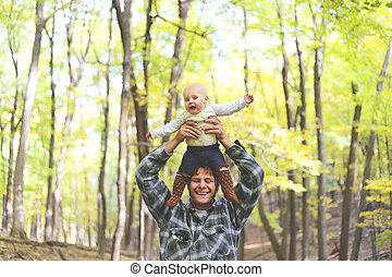 Happy Father Playing with Cute Baby daughter in Autumn Woods