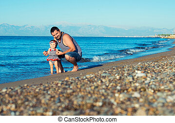 Happy father playing with cute little daughter at the beach