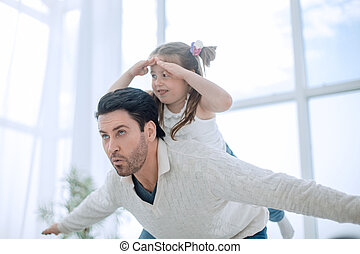happy father playing with daughter in the bright living room