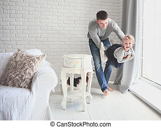 happy father playing with his baby daughter in the bright living