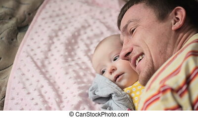 Happy father playing with his baby daughter on the bed in the bedroom