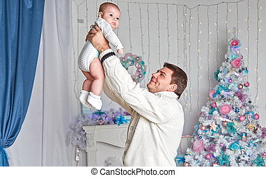 happy father playing with little son near Christmas tree .