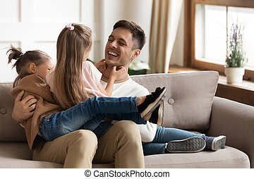 Happy father playing with two daughters, tickling on couch...