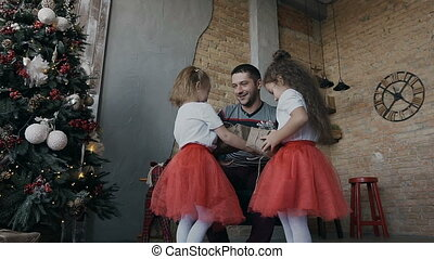 Happy father presents presents to his two daughters on Christmas Eve. Happy children with gifts