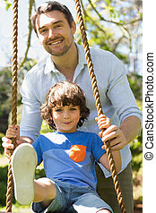 Happy father pushing boy on swing